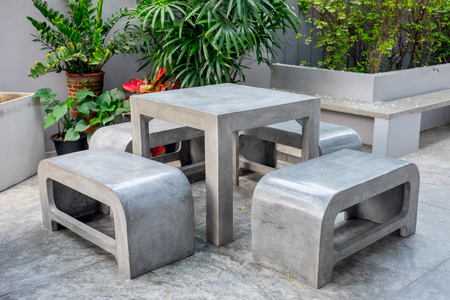 vintage furniture: Concrete outdoor furniture set in the small garden including on table and four benches Stock Photo