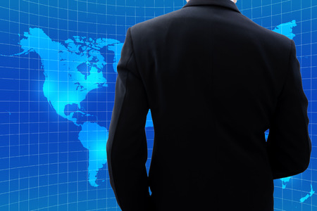 world thinking: Isolated back side of businessman in dark gray suit when he is looking at world map and thinking about global business