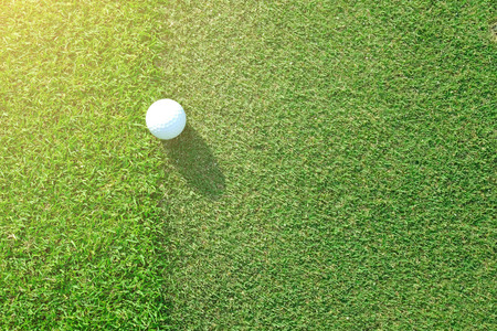 fringe: Golf ball sitting between apron fringe and green under afternoon sunlight Stock Photo