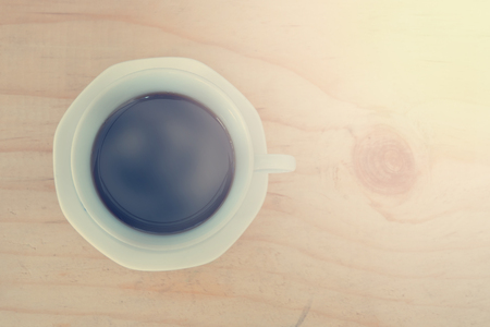 very good: Cup of coffee on wooden table with smooth steam on the top make it feel very good smell - vintage effect