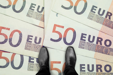 financial world: black shoes standing on money bills in the global business and financial world