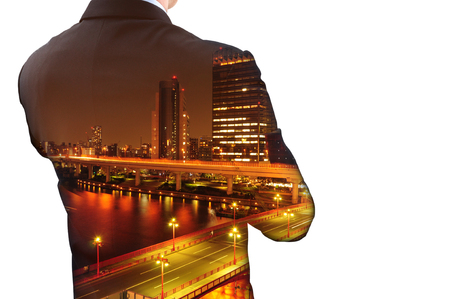 Isolated double exposure of businessman in suit and cityscape at night. Hes looking for his success in business and idea for life