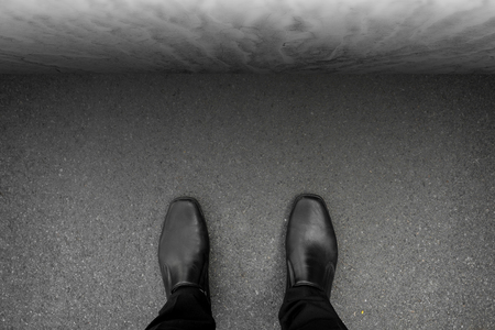 no way: black shoes standing at the deadlock, in front of him is concrete wall, no way to go, no way out.