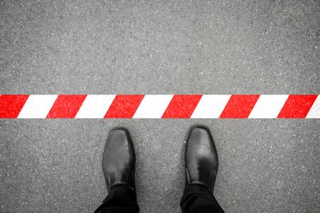 黒の靴は、赤白のラインに立っています。ラインを通過しません。それは禁止が、許可されません。それは制限されます。それは終わりです。 写真素材