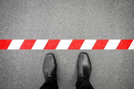 do not cross: black shoes standing at the red-white line. Do not cross the line. Its prohibited and not allowed. Its limited. Its the end.