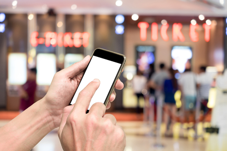 One booking movie ticket via smart phone. Ticket selling machine in the background