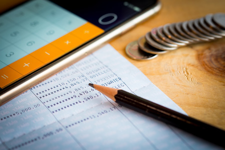 account statements: Savings account bank book, pencil and smartphone used as calculator on wooden table Stock Photo