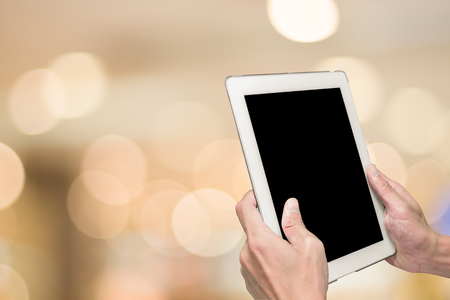 departmentstore: One using white tablet pc and abstract blur warm light in background