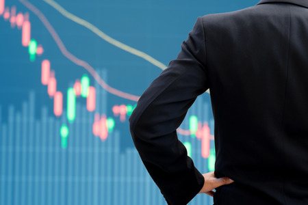 akimbo: Back side of businessman in dark gray suit standing and akimbo watching stock market lowering down graph as it becomes bear market Stock Photo