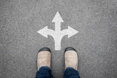 ブラウンの靴どの道を行くの意思交差道路に立っています。選択する 3 つの方法
