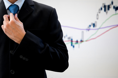rearrange: Businessman in dark gray suit rearrange his neck tie for important meeting and business deal. Global economic and stock market chart in the background
