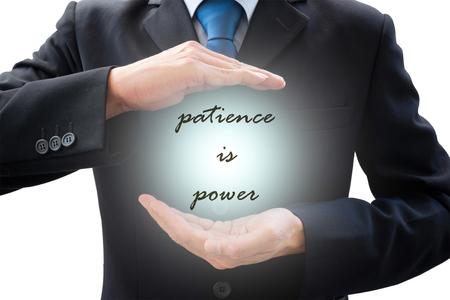 """paciencia: Aislado hombre de negocios en traje gris oscuro y la luz de poder entre sus manos y cita """"la paciencia es poder"""""""