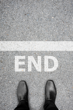 end of the line: Businessman in black shoes standing at the end line on asphalt concrete floor. Representing that its time to stop and turn back on his business