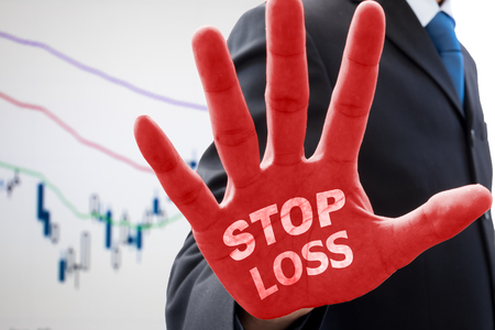 winning stock: Businessman in dark gray suit raise his hand in action of stop and words  stop loss  on his red palm. Telling how to stop loss from businss risk and stock market crash. Global economic and market chart in the background