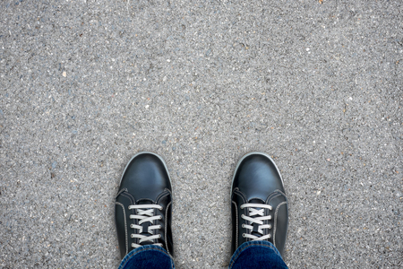 Black casual shoes standing on asphalt concrete floor making decision what to do next.