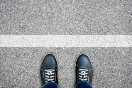 turn back: Black casual shoes standing at the white line making decision - stop and turn back or across the line and go further Stock Photo