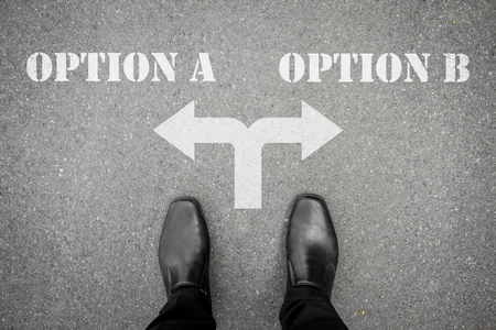 start to cross: Businessman in black shoes standing at the crossroad making decision which way to go - option A or option B