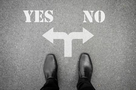 どの道を行く - はいの意思交差点またはなしに立っている黒い靴のビジネスマン