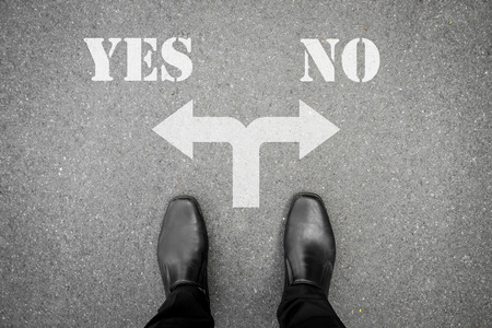 Businessman in black shoes standing at the crossroad making decision which way to go - yes or no Imagens