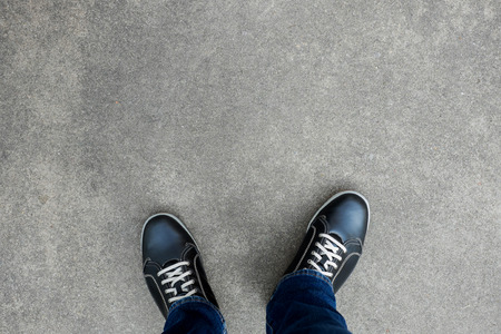Black casual shoes standing and resting on asphalt concrete floor. Making decision what to do next Imagens - 58888577