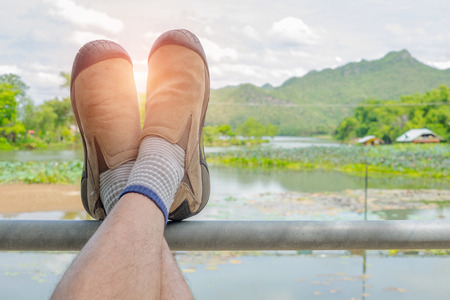 sight seeing: A man wearing brown suede shoes place his feet upon roll bar and relax in front of nature sight seeing view. Mountain, river and cloudy summer sky. Sunlight shining between his feet. Stock Photo