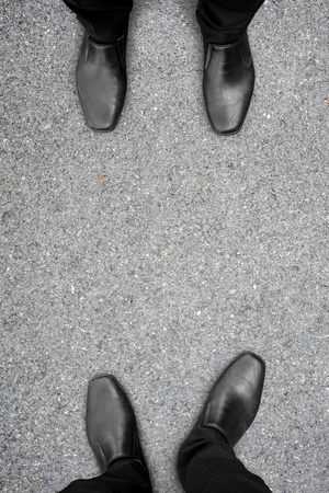 rivals: Two businessmen in black shoes standing on opposite sides. They are competitors, friends, rivals, enemies or partner.