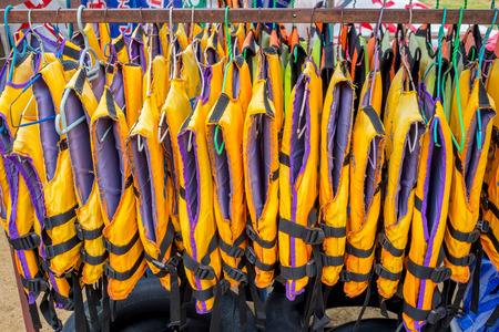 Lot of life jackets hanging on the rack. For rent, rental. For tourist to rent if they feel not safety to swim in the sea or river. Banco de Imagens