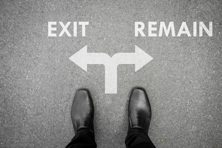 remain: Businessman in black shoes standing at the crossroad making decision which way to go - exit or remain