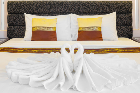 honeymoon suite: Hotel double bed with towels prepare for new customer, lovers, just married couple. The towels are folded in shape of two swans and heart. Two white pillows and two small gold pillow. Focus on towels. Stock Photo