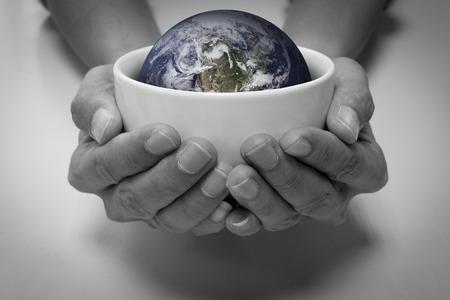 Le persone affamate e la terra in una ciotola di ceramica bianca. Terra concettuale risparmio, ambiente di risparmio, la cura della terra, cura le persone, di aiuto e condividere, la fame e le persone che soffrono la fame.