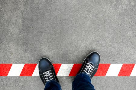 赤と白のラインに立っている黒のカジュアル シューズ。制限を横断します。背くし、ルールに反する行為。