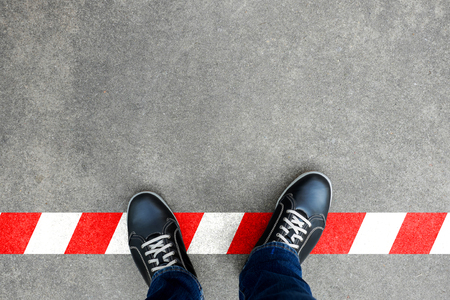 Black casual shoes standing on red and white line. Crossing the limit. Disobey and act against the rule. Archivio Fotografico