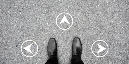 黒の靴は、意思決定どの道を行く - 3 つの方法を選択する岐路に立っています。白い円形のコンクリートの床に方向標識。 写真素材