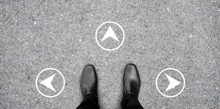 black shoes standing at the crossroad making decision which way to go - three ways to choose. White round direction sign on the concrete floor.