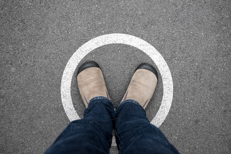 floor standing: A man wearing brown suede shoes and blue jeans standing in white circle on asphalt concrete floor. Standing in boundary limit and never think different.