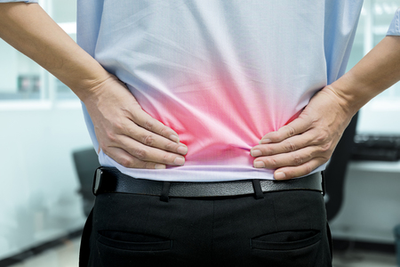 herniated: A man in blue shirt feeling pain on his back. Office syndrome. Back pain from work. Herniated nucleus pulposus. spine pain. spinal degeneration. Stock Photo