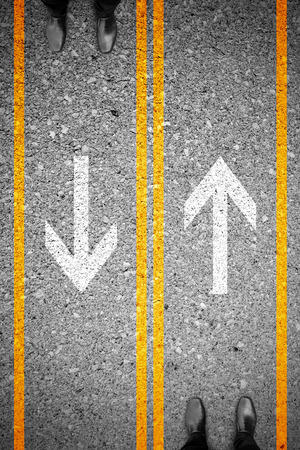 rivals: Two businessmen standing on different side of the road. Representing rivals, enemys, competitors in business and life. Stock Photo