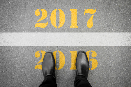 Black shoes standing at the line between last year 2016 and new year 2017