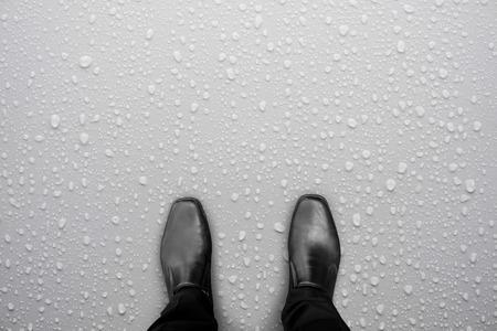 흰색 젖은 바닥에 검은 신발 서에서 사업가. 바닥에 워터 드롭입니다. 주의, 미끄러운 바닥. 스톡 콘텐츠