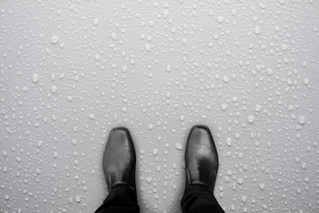 Businessman in black shoes standing on white wet floor. Water drop on the floor. Caution, slippery floor.