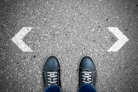 which way: Black casual shoes standing at the crossroad making decision which way to go.