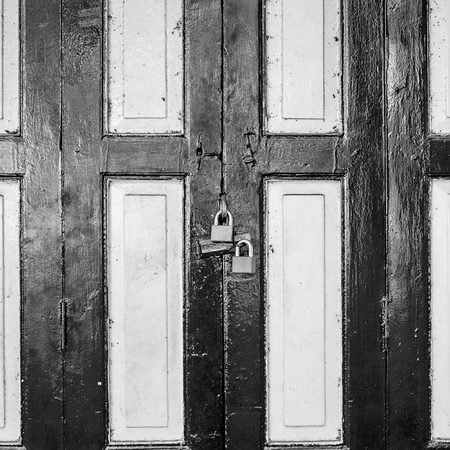 monotone: Old style black and white wooden door in Bangkok, Thailand and key locked. Vintage and monotone effect. Stock Photo