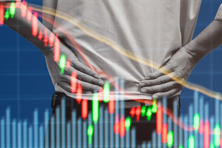 Double exposure of businessman standing and akimbo and stock market lowering down graph as it becomes bear market and bad economy. Stock Photo