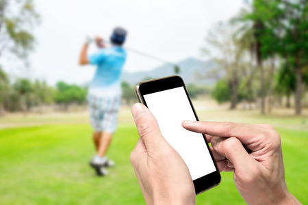 computer club: One using smartphone when other swinging on golf teeing ground.