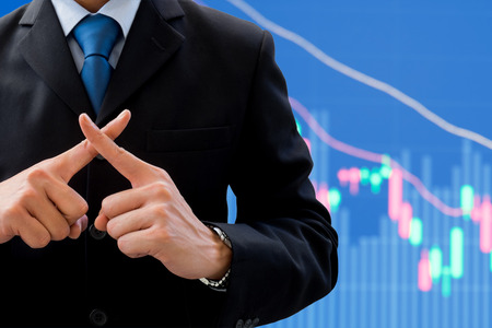 Businessman in dark gray suit using his hands as cross. Meaning wrong, fault, not correct, not allow, prohibit. Global business and stock market decreasing down in background. Stock Photo