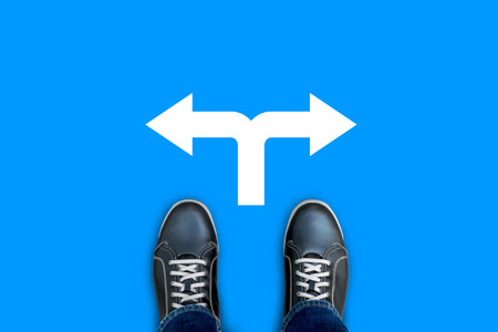 Black casual shoes standing on blue floor at the crossroad making decision which way to go. Left or right.