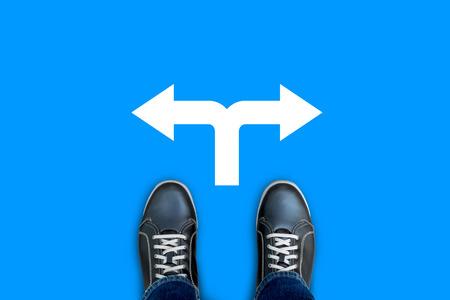 Zwarte toevallige schoenen staan ??op blauwe vloer op het kruispunt maken beslissing welke weg te gaan. Links of rechts. Stockfoto - 65840924