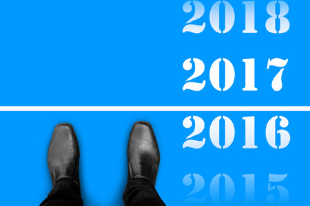 Black shoes standing at the line between last year 2016 and happy new year 2017 Standard-Bild
