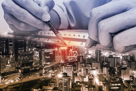 quantity: Double exposure of engineer are measuring distance in drawing paper and city at night. Representing engineer and architecture work is building the world of design and construction. Stock Photo