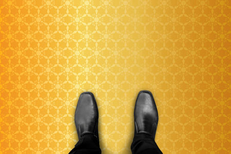 millonario: Rich and wealthy millionaire businessman in black shoes standing on gold geometric pattern floor.